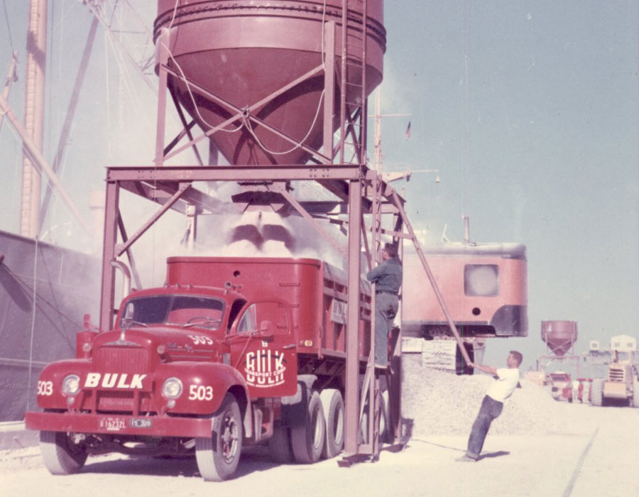 Bulk Team Members in Action Loading Material Onto a Red Dump Truck