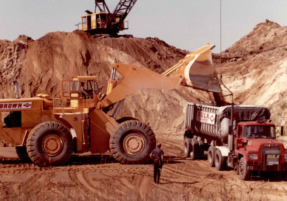 Brown's Bulldozer And Crane Loading Dirt Onto Bulk Transport Dump Truck