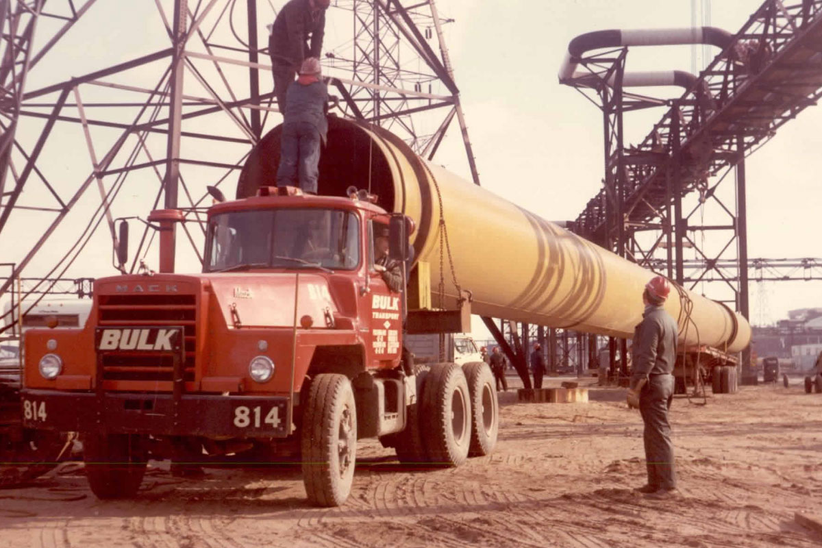 Bulk Transport Crew Loading Large Pipe Onto Truck Back In The Day