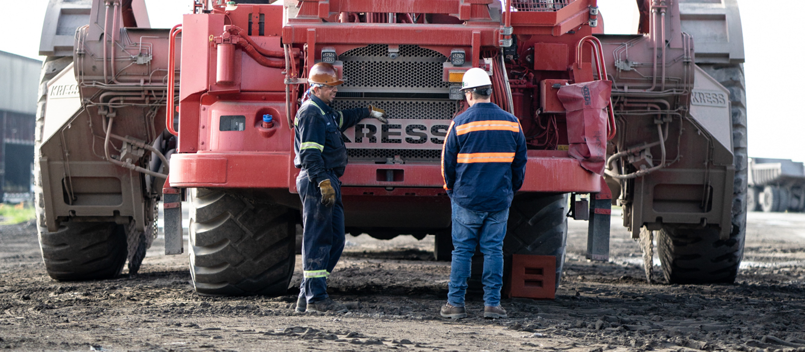 Two Employees Wearing Hard Hats And Neon Safety Vests Standing In Front Of Red Kress Heavy Equipment At Project Site
