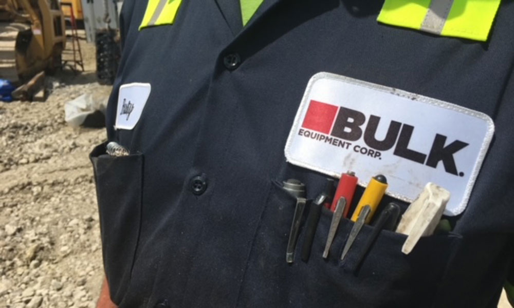 Close Up Of Bulk Equipment Corp. Logo On A Uniform