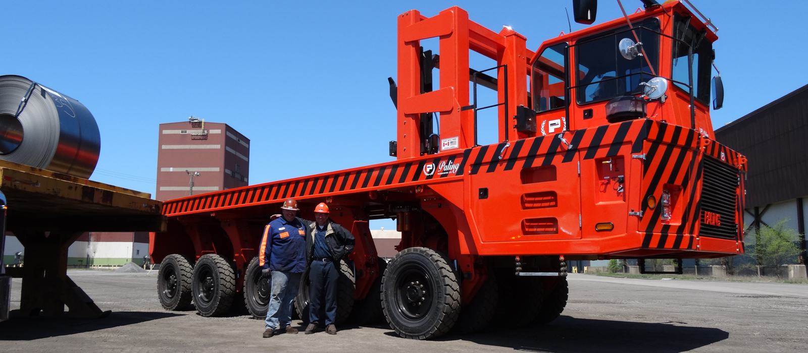 Two Bulk Equipment Corp. Employees Wearing Hard Hats Standing In Front Of A Bright Red Transporter