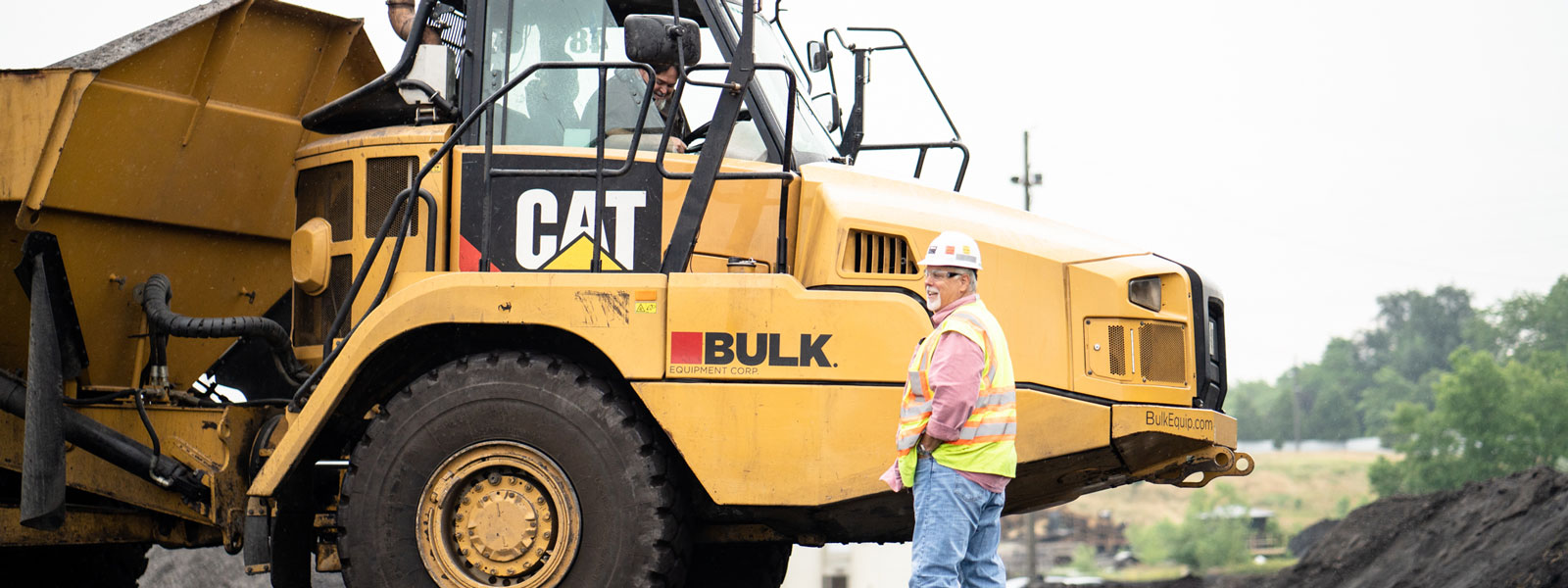 Bulk Equipment Employee Wearing Hard Hat, Neon Vest & Safety Glasses Next To Cat® Heavy Equipment At A Landfill Job Site