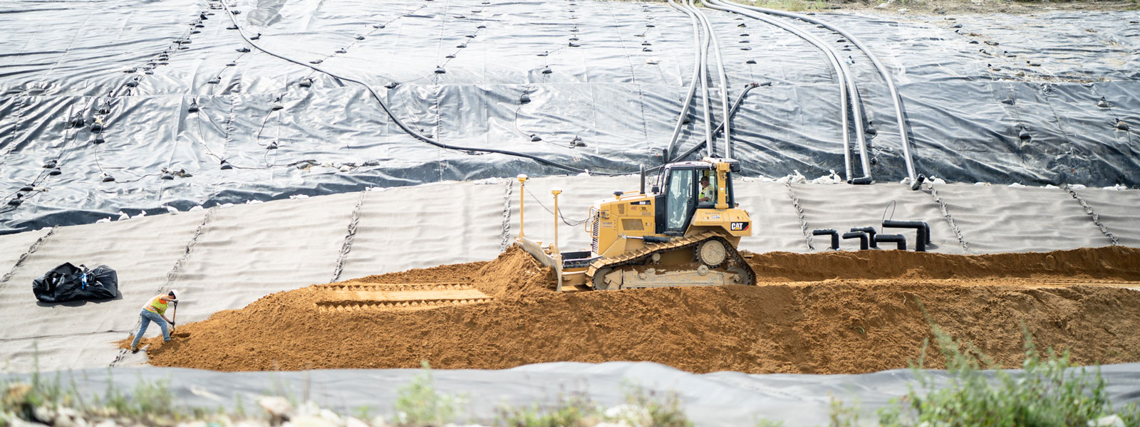 Cat® Bulldozer & Bulk Employee Moving Dirt To Cover Solid Waste At A Landfill Site